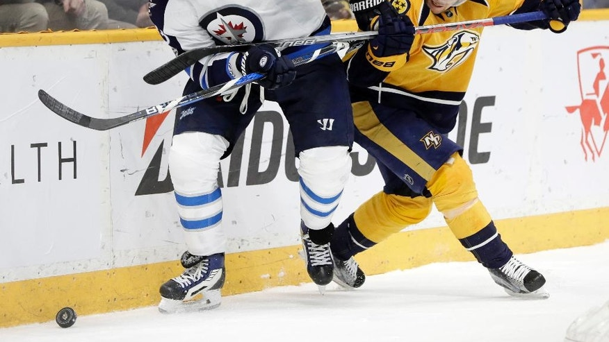 Winnipeg Jets defenseman Dustin Byfuglien (33) and Nashville Predators left wing Viktor Arvidsson (38), of Sweden, battle for the puck during the second period of an NHL hockey game, Monday, March 13, 2017, in Nashville, Tenn. (AP Photo/Mark Humphrey)