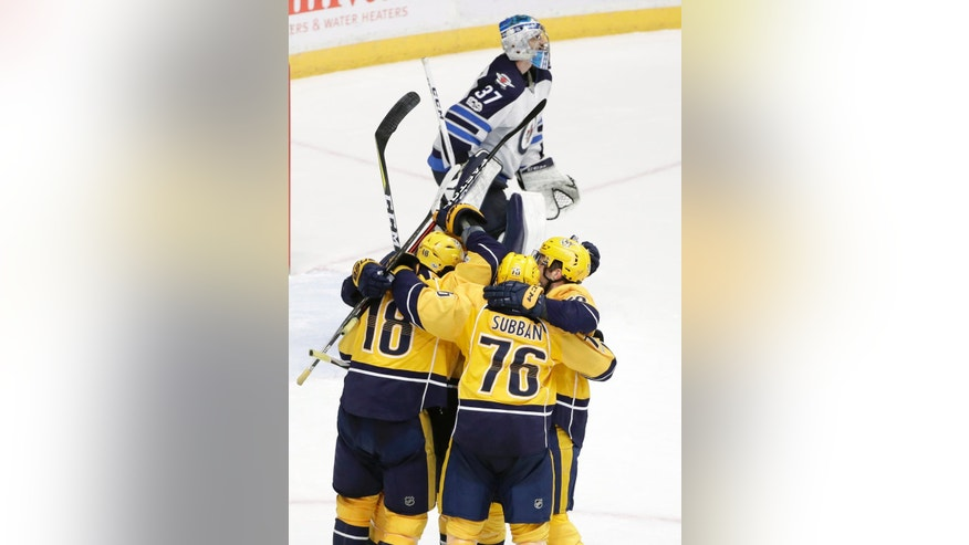 Nashville Predators right wing James Neal (18) celebrates with teammates including P.K. Subban (76) as Winnipeg Jets goalie Connor Hellebuyck (37) leaves the ice after Neal scored the winning goal during overtime in an NHL hockey game, Monday, March 13, 2017, in Nashville, Tenn. The Predators won 5-4. (AP Photo/Mark Humphrey)
