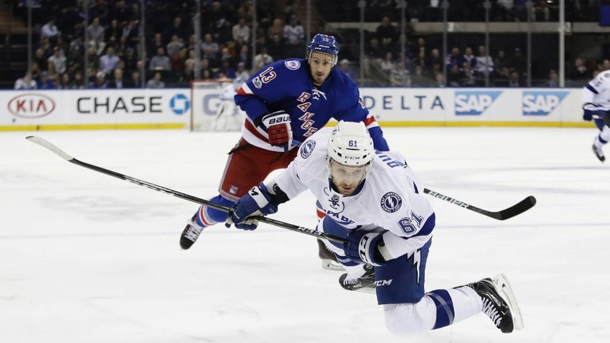 Tampa Bay Lightning's Gabriel Dumont (61) trips while fighting for the puck as New York Rangers' Kevin Hayes (13) watches during the first period of an NHL hockey game, Monday, March 13, 2017, in New York. (AP Photo/Frank Franklin II)