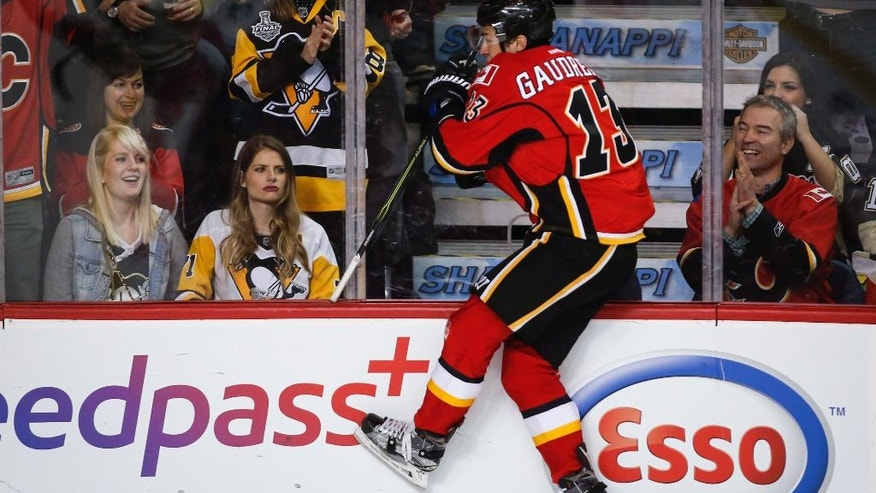 Pittsburgh Penguins fans look on as Calgary Flames left wing Johnny Gaudreau (13) celebrates his goal during third period NHL hockey action in Calgary, Monday, March 13, 2017. (Jeff McIntosh/The Canadian Press via AP)