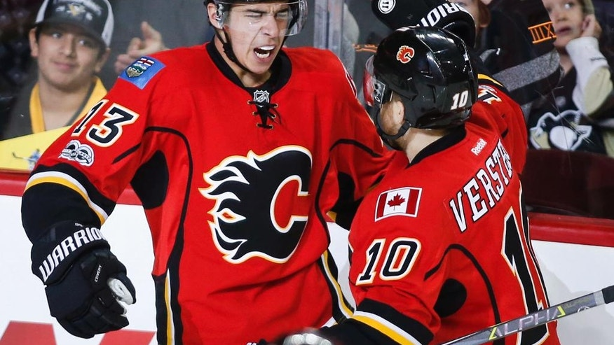 Calgary Flames left wing Johnny Gaudreau (13) celebrates his goal with right wing Kris Versteeg (10) during third period NHL hockey action against the Pittsburgh Penguins in Calgary, Monday, March 13, 2017. (Jeff McIntosh/The Canadian Press via AP)