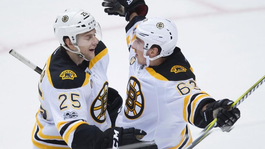 Boston Bruins defenseman Brandon Carlo (25) and left wing Brad Marchand (63) celebrate Marchand's second goal against the Vancouver Canucks during the third period of an NHL hockey game in Vancouver, British Columbia, Monday, March 13, 2017. (Darryl Dyck/The Canadian Press via AP)