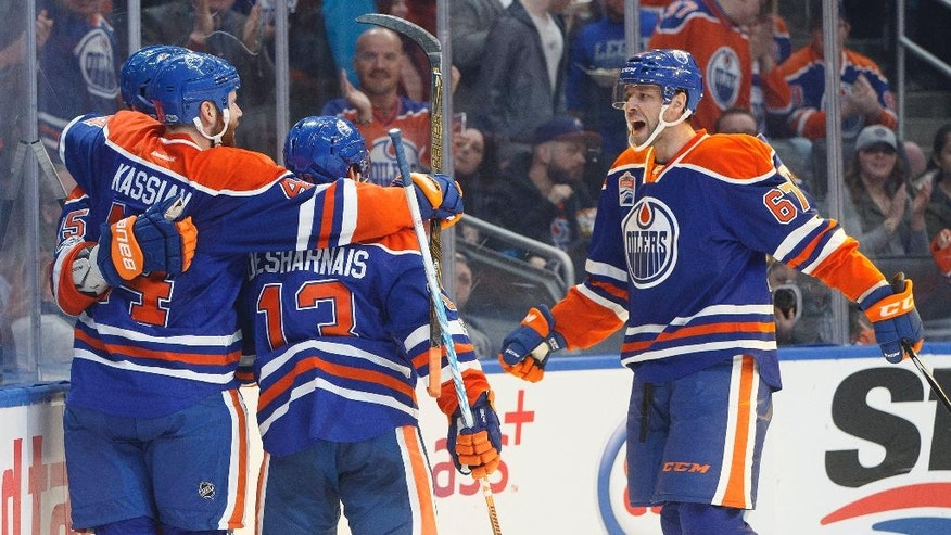 Edmonton Oilers' Zack Kassian (44), David Desharnais (13) and Benoit Pouliot (67) celebrate a goal against the Dallas Stars during second period NHL hockey action in Edmonton, Alberta, Tuesday, March 14, 2017. (Jason Franson/The Canadian Press via AP)