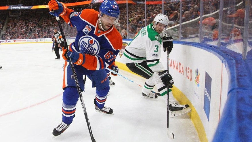 Dallas Stars' John Klingberg (3) and Edmonton Oilers' Benoit Pouliot (67) vie in the corner for the puck during second period NHL hockey action in Edmonton, Alberta, Tuesday, March 14, 2017. (Jason Franson/The Canadian Press via AP)