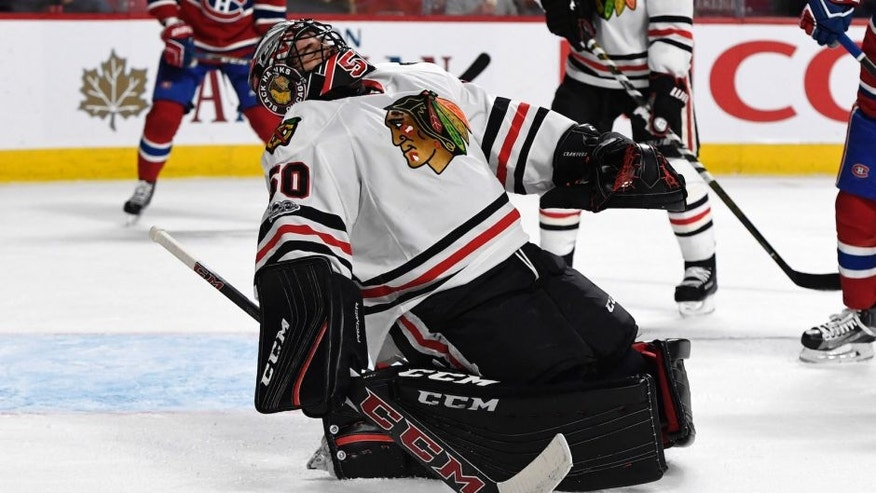 Mar 14, 2017; Montreal, Quebec, CAN; Chicago Blackhawks goalie Corey Crawford (50) reacts after getting hit in the face-mask by a shot during the second period of the game against the Montreal Canadiens at the Bell Centre. Mandatory Credit: Eric Bolte-USA TODAY Sports