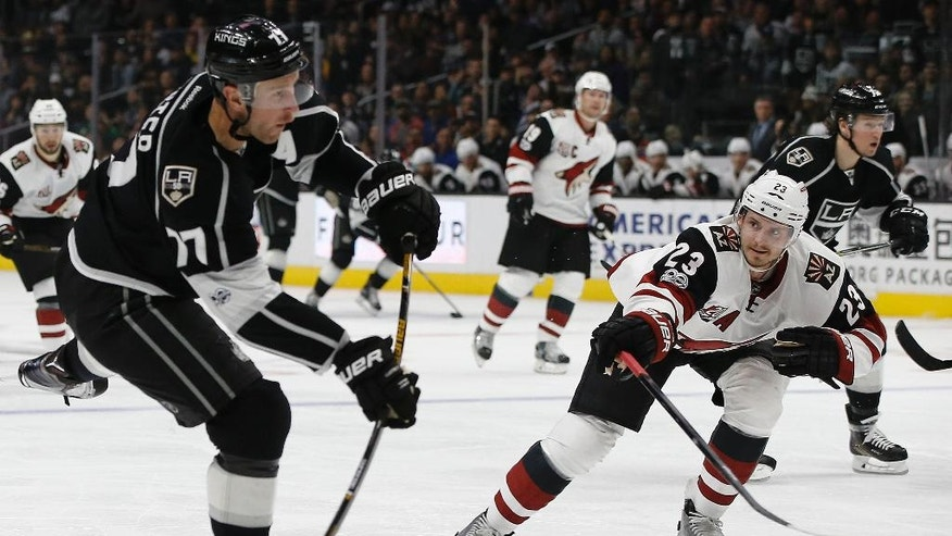 Los Angeles Kings center Jeff Carter, left, shoots as Arizona Coyotes defenseman Oliver Ekman-Larsson (23), of Sweden, defends during the second period of an NHL hockey game in Los Angeles, Tuesday, March 14, 2017. (AP Photo/Alex Gallardo)