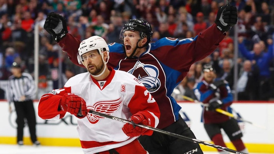Colorado Avalanche left wing J.T. Compher, back, celebrates after scoring a goal as Detroit Red Wings left wing Tomas Tatar, of Slovakia, skates away during the third period of an NHL hockey game Wednesday, March 15, 2017, in Denver. The Avalanche won 3-1. (AP Photo/David Zalubowski)