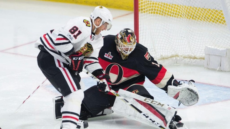 Ottawa Senators goalie Mike Condon keeps his eyes on the puck as Chicago Blackhawks right wing Marian Hossa tries to score during the third period in an NHL hockey game in Ottawa, Ontario, Thursday, March 16, 2017. (Adrian Wyld/The Canadian Press via AP)