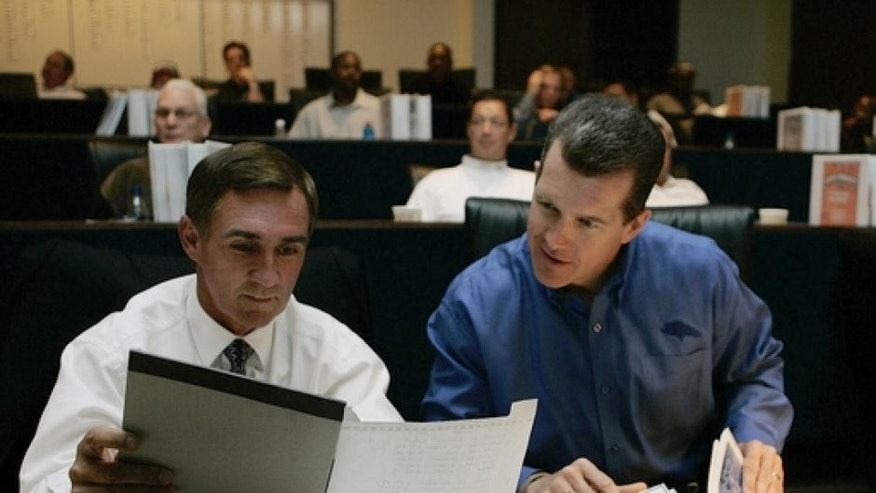 "FILE - In this April 29, 2006 file photo, Denver Broncos head coach Mike Shanahan, left, and general manager Ted Sundquist compare notes in the draft room at the Broncos headquarters during the opening round of the NFL draft in Denver. When the Green Bay Packers decided to give Brett Favre the NFL's first $100 million contract in 2001 _ well, first ""$100 million contract,"" because, like so many deals in the league, it wasn't ultimately worth the advertised amount _ the team structured it to create extra space under the salary cap for other signings. (AP Photo/Ed Andrieski, File)"