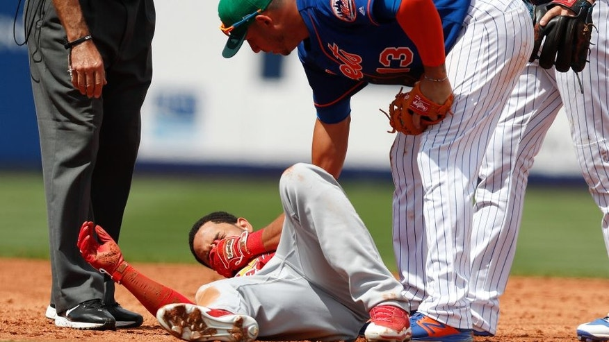 New York Mets shortstop Asdrubal Cabrera, right, checks on St. Louis Cardinals' Tommy Pham, left, after he was injured being tagged out in a rundown during the third inning of a spring training baseball game Friday, March 17, 2017, in Port St. Lucie, Fla. Pham left he field under his power. (AP Photo/John Bazemore)