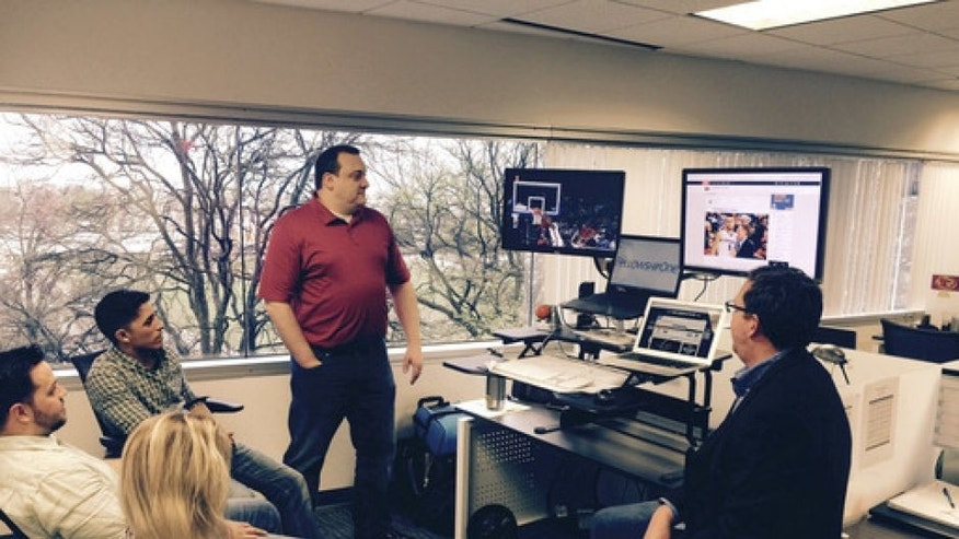 In this Thursday, March 16, 2017 photo, Chris Nelson, right, Jessica Knight, second from right, Bobby Lester, third from right, Rick Miner, fourth from right, and Ted Wlazlowski watch the NCAA men's basketball tournament on laptop computers from their office at FellowshipOne in Dallas. Turner Sports says that streaming March Madness games digitally on smart phones, tablets and computers is becoming increasingly popular with 29 million video startups on Thursday, the first full day of tournament action. That's a 19 percent increase from last year. (Dave Nagel via AP)