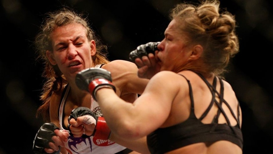 LAS VEGAS, NV - DECEMBER 28: (L-R) Miesha Tate punches Ronda Rousey in their UFC women's bantamweight championship bout during the UFC 168 event at the MGM Grand Garden Arena on December 28, 2013 in Las Vegas, Nevada. (Photo by Josh Hedges/Zuffa LLC/Zuffa LLC via Getty Images)