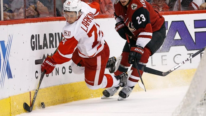 Detroit Red Wings center Dylan Larkin (71) gets tripped up by Arizona Coyotes defenseman Oliver Ekman-Larsson (23) during the second period of an NHL hockey game Thursday, March 16, 2017, in Glendale, Ariz. (AP Photo/Ross D. Franklin)