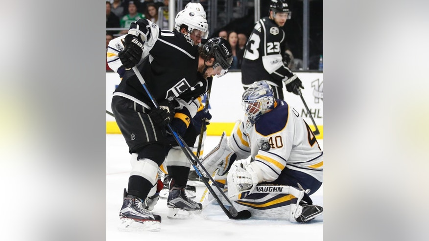 Los Angeles Kings' Anze Kopitar, left, of Slovenia, looks at the puck stuck on the sleeve of Buffalo Sabres goalie Robin Lehner's jersey during the second period of an NHL hockey game Thursday, March 16, 2017, in Los Angeles. (AP Photo/Jae C. Hong)