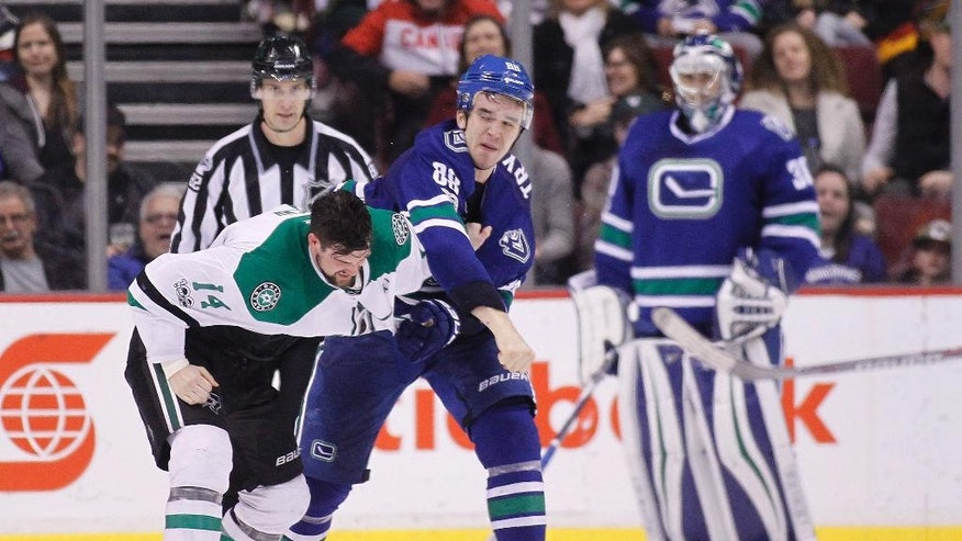 Dallas Stars' Jamie Benn (14) mixes it up with Vancouver Canucks' Nikita Tryamkin (88) during the second period of an NHL hockey game Thursday, March 16, 2017, in Vancouver, British Columbia. (Ben Nelms/The Canadian Press via AP)