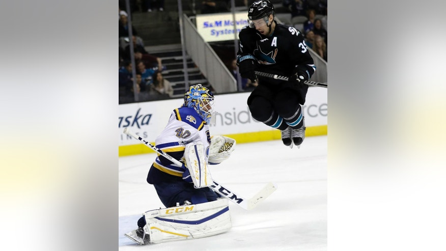 St. Louis Blues goalie Carter Hutton, left, stops a shot next to San Jose Sharks' Logan Couture during the second period of an NHL hockey game Thursday, March 16, 2017, in San Jose, Calif. (AP Photo/Marcio Jose Sanchez)