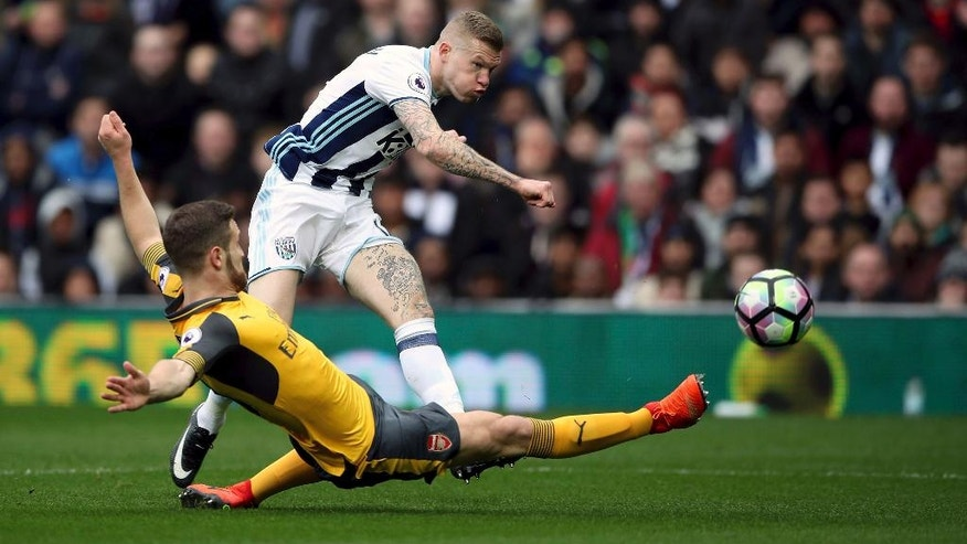 West Bromwich Albion's James McClean shoots as Arsenal's Shkodran Mustafi attempts to block, during the English Premier League soccer match between West Bromwich Albion and Arsenal,  at The Hawthorns, in West Bromwich, England, Saturday March 18, 2017.  (Nick Potts/PA via AP)