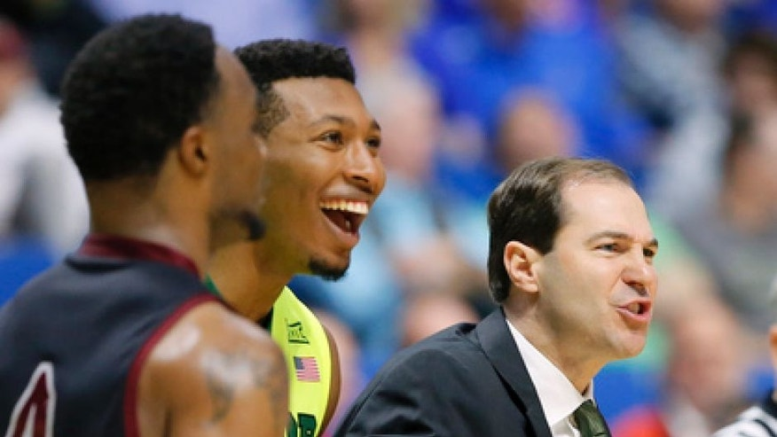 New Mexico State's Ian Baker (4) walks up court as Baylor's King McClure, center, and head coach Scott Drew, right, celebrate during a time out in the second half of a first-round game in the men's NCAA college basketball tournament in Tulsa, Okla., Friday March 17, 2017. (AP Photo/Tony Gutierrez)