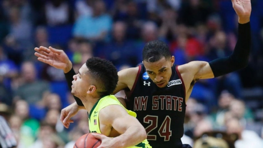 Baylor guard Manu Lecomte, front, is fouled by New Mexico State guard Matt Taylor (24) in the second half of a first-round game in the men's NCAA college basketball tournament in Tulsa, Okla., Friday, March 17, 2017. Baylor won 91-73. (AP Photo/Sue Ogrocki)