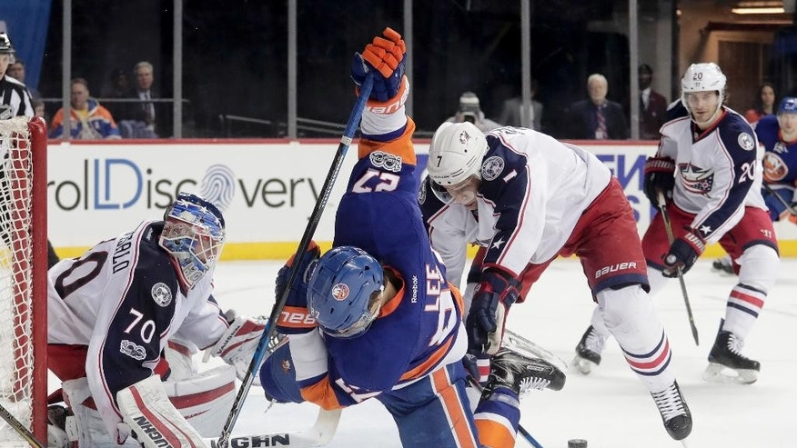 New York Islanders left wing Anders Lee (27) trips as he looks to score off a rebound against Columbus Blue Jackets defenseman Jack Johnson (7) and goalie Joonas Korpisalo (70) during the second period of an NHL hockey game, Saturday, March 18, 2017, in New York. (AP Photo/Julie Jacobson)