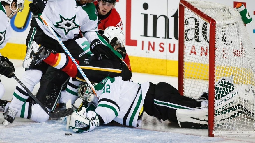 Dallas Stars goalie Kari Lehtonen, bottom, of Finland, reaches for the puck as teammate Patrik Nemeth, left, of Sweden, checks Calgary Flames' Lance Bouma during the second period of an NHL hockey game in Calgary, Alberta, Friday, March 17, 2017. (Jeff McIntosh/The Canadian Press via AP)