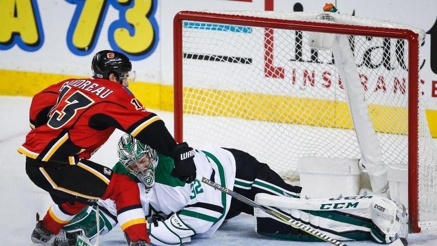 Dallas Stars goalie Kari Lehtonen, right, of Finland, blocks the net on Calgary Flames' Johnny Gaudreau during the second period of an NHL hockey game in Calgary, Alberta, Friday, March 17, 2017. (Jeff McIntosh/The Canadian Press via AP)