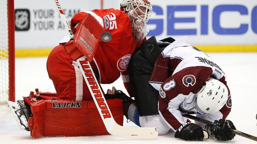 Detroit Red Wings goalie Jimmy Howard (35) stops a shot as Colorado Avalanche center Joe Colborne (8) falls in the first period of an NHL hockey game Saturday, March 18, 2017, in Detroit. (AP Photo/Paul Sancya)