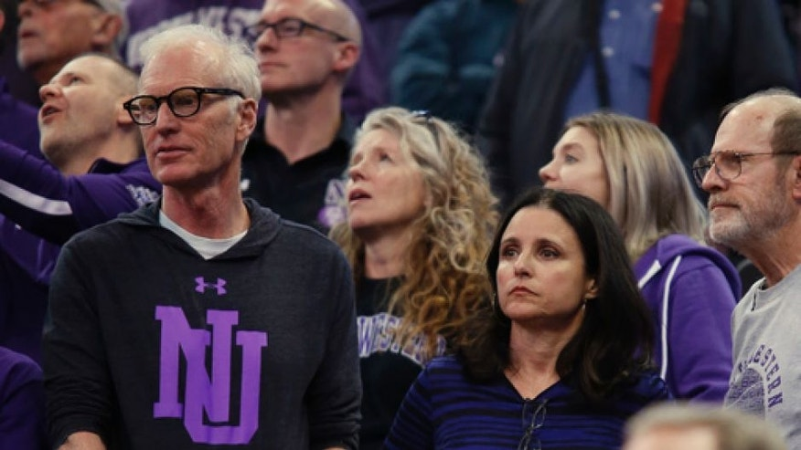 Actress Julia Louis-Dreyfus, lower right, and her husband, producer and writer Brad Hall, left, watch Northwestern play Vanderbilt during a first-round game of the NCAA men's college basketball tournament Thursday, March 16, 2017, in Salt Lake City. Northwestern won 68-66. (AP Photo/George Frey)