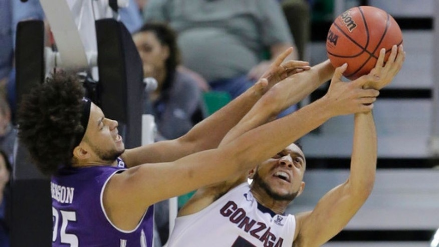 Gonzaga guard Nigel Williams-Goss (5) and Northwestern center Barret Benson (25) battle for a rebound during the first half of a second-round college basketball game in the men's NCAA Tournament Saturday, March 18, 2017, in Salt Lake City. (AP Photo/Rick Bowmer)