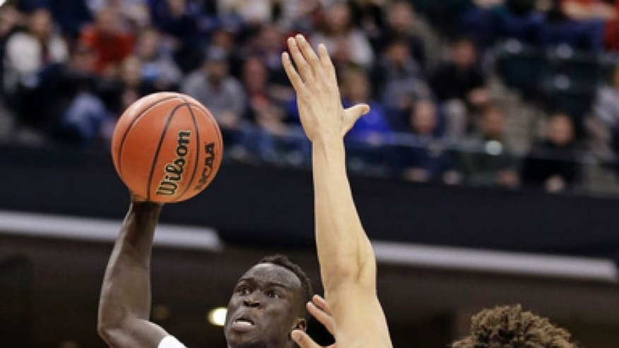 Louisville forward Deng Adel (22) goes up for a dunk over Michigan forward D.J. Wilson (5) during the first half of a second-round game in the men's NCAA college basketball tournament in Indianapolis, Sunday, March 19, 2017. (AP Photo/Michael Conroy)