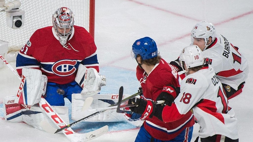 Ottawa Senators' Alexandre Burrows (14) shoots against Montreal Canadiens goaltender Carey Price as Canadiens' Nathan Beaulieu (28) and Senators' Ryan Dzingel look for the rebound during second-period NHL hockey game action in Montreal, Sunday, March 19, 2017. (Graham Hughes/The Canadian Press via AP)