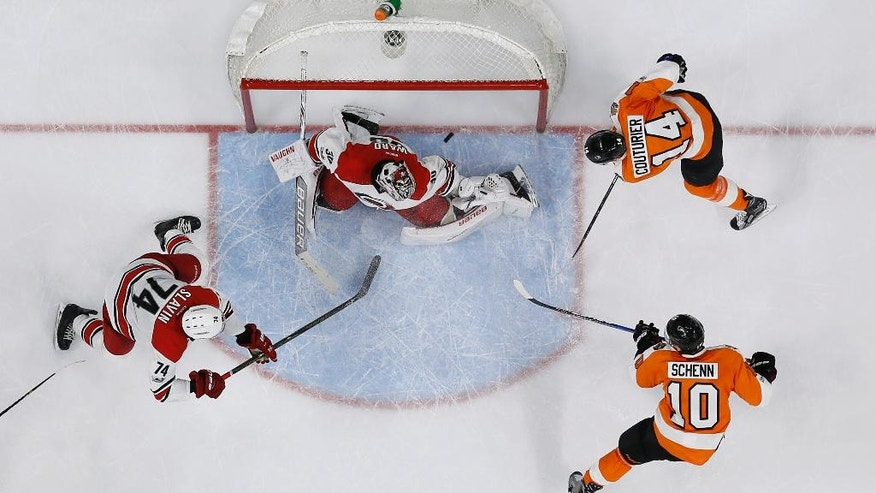 Philadelphia Flyers' Brayden Schenn (10) scores past Carolina Hurricanes' Cam Ward (30) as Sean Couturier (14) and Jaccob Slavin (74) watch during overtime of an NHL hockey game, Sunday, March 19, 2017, in Philadelphia. Philadelphia won 4-3. (AP Photo/Matt Slocum)
