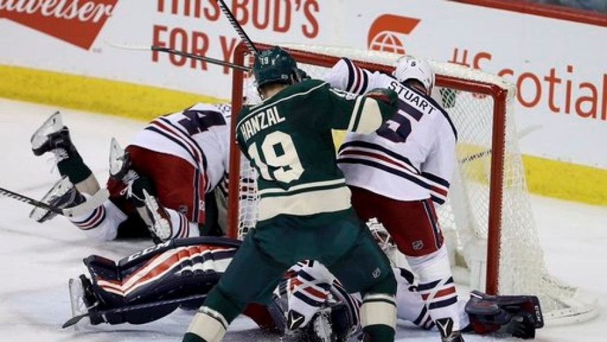 Winnipeg Jets goaltender Michael Hutchinson (34) stretches out and makes a save with Jets' Mark Stuart (5) battling Minnesota Wild's Martin Hanzal (19) in front of the net during the third period of an NHL hockey game in Winnipeg, Manitoba, Sunday, March 19, 2017. (Trevor Hagan/The Canadian Press via AP)