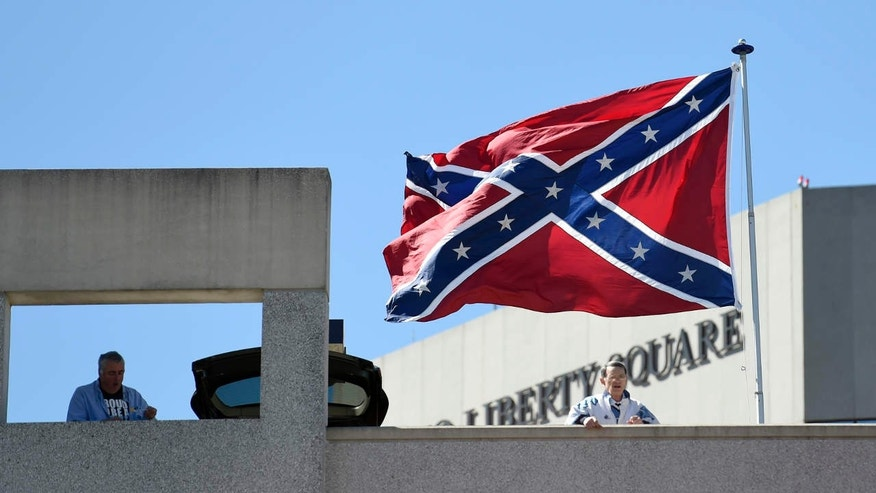 March 19, 2017: Basketball fans look out as a Confederate flag flies from a parking deck outside the arena before a second-round game of the NCAA men's college basketball tournament in Greenville, S.C..