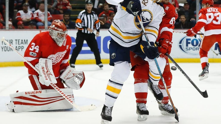 Detroit Red Wings' Xavier Ouellet, right, defends Buffalo Sabres Marcus Foligno as a shot is deflected towards goalie Petr Mrazek in the first period of an NHL hockey game Monday, March 20, 2017, in Detroit. (AP Photo/Paul Sancya)