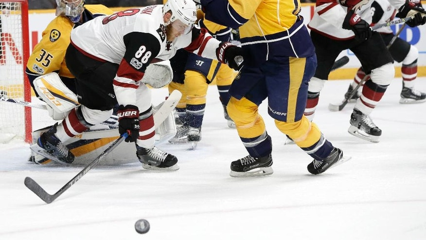 Arizona Coyotes left wing Jamie McGinn (88) and Nashville Predators center Mike Fisher (12) chase after a rebound during the first period of an NHL hockey game Monday, March 20, 2017, in Nashville, Tenn. (AP Photo/Mark Humphrey)