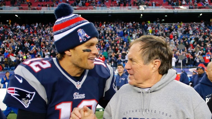 Dec 14, 2014; Foxborough, MA, USA; New England Patriots quarterback Tom Brady (12) celebrates with head coach Bill Belichick (R) after clinching the AFC East title with a 41-13 win over the Miami Dolphins at Gillette Stadium. Mandatory Credit: Winslow Townson-USA TODAY Sports
