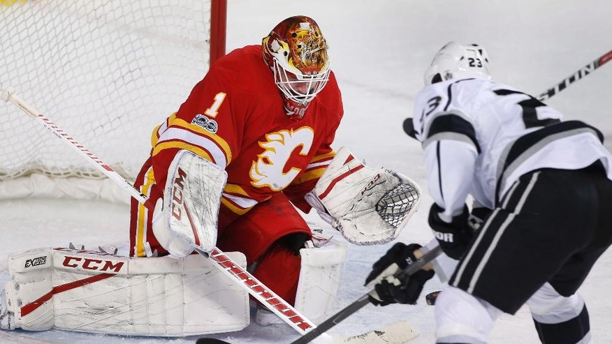 Calgary Flames goalie Brian Elliott, left, makes a save against Los Angeles Kings' Dustin Brown during the second period of an NHL hockey game in Calgary, Alberta, Sunday, March 19, 2017.  (Larry MacDougal/The Canadian Press via AP)