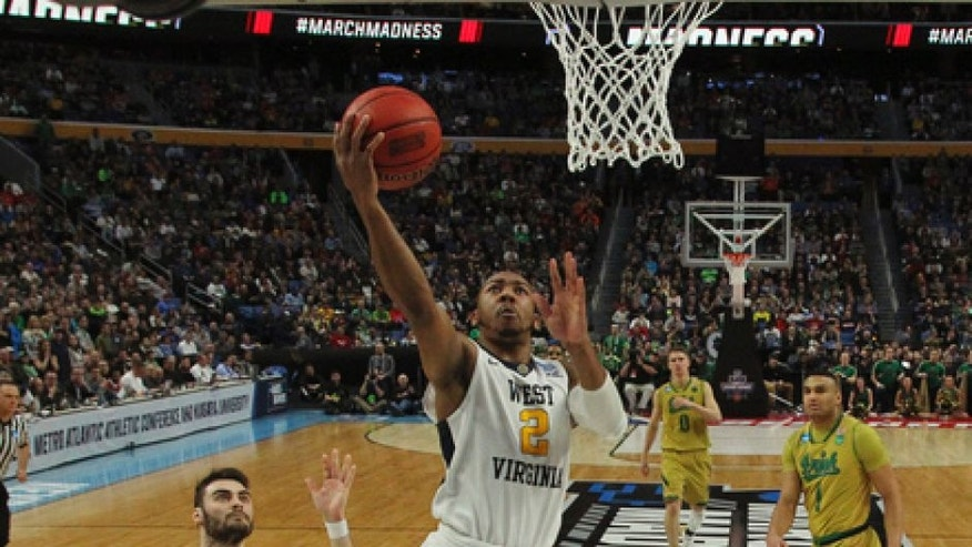 West Virginia guard Jevon Carter (2) drives to the basket against Notre Dame forward guard Matt Farrell (5) during the second half of a second-round men's college basketball game in the NCAA Tournament, Saturday, March 18, 2017, in Buffalo, N.Y. West Virginia won, 83-71. (AP Photo/Bill Wippert)