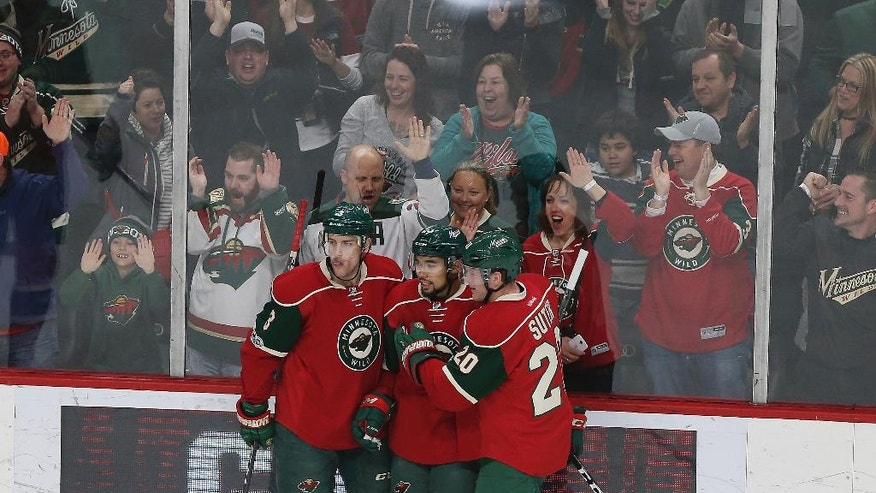 Minnesota Wild's Matt Dumba, center, celebrates with teammates Charlie Coyle, left, and Ryan Suter after Dumba's goal against the San Jose Sharks in the first period of an NHL hockey game Tuesday, March 21, 2017, in St. Paul, Minn. (AP Photo/Stacy Bengs)