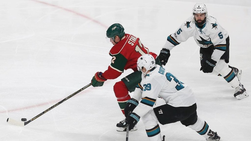 Minnesota Wild's Eric Staal (12) pushes the puck out in front of San Jose Sharks' Logan Couture (39) and David Schlemko (5) in the first period of an NHL hockey game Tuesday, March 21, 2017, in St. Paul, Minn. (AP Photo/Stacy Bengs)