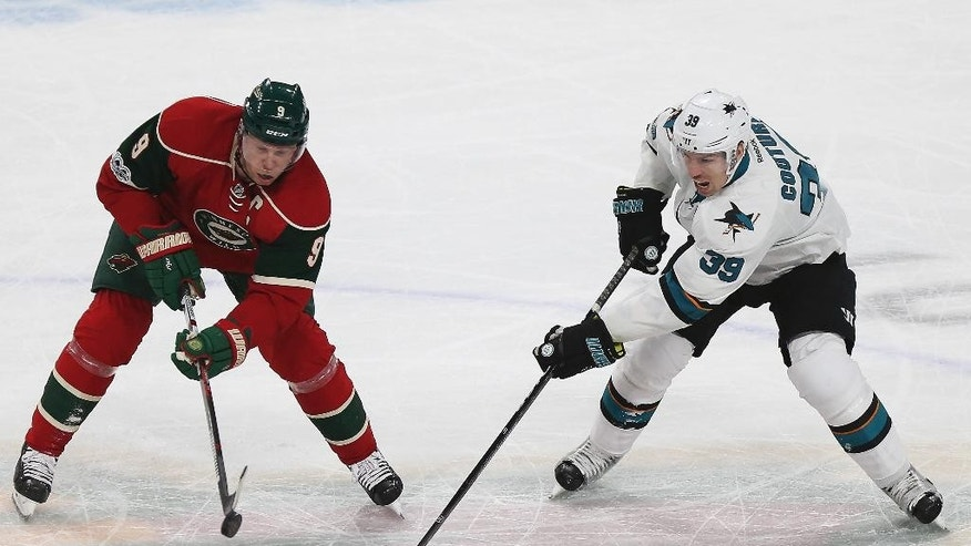 Minnesota Wild's Mikko Koivu, left, controls the puck against San Jose Sharks' Logan Couture in the first period of an NHL hockey game Tuesday, March 21, 2017, in St. Paul, Minn. (AP Photo/Stacy Bengs)