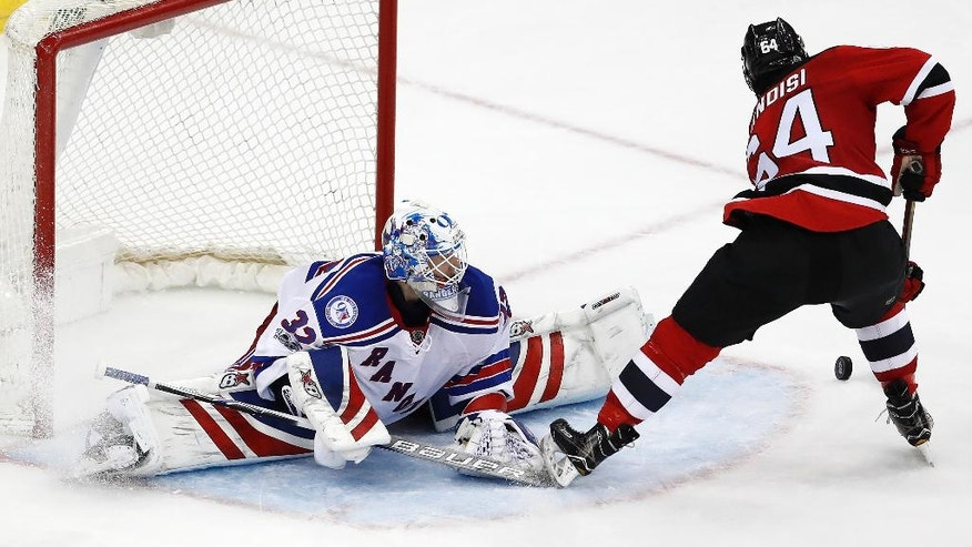 New Jersey Devils left wing Joseph Blandisi (64) makes a move on New York Rangers goalie Antti Raanta (32), of Finland, to score the game winning goal during the overtime of an NHL hockey game, Tuesday, March 21, 2017, in Newark, N.J. The Devils won 3-2. (AP Photo/Julio Cortez)