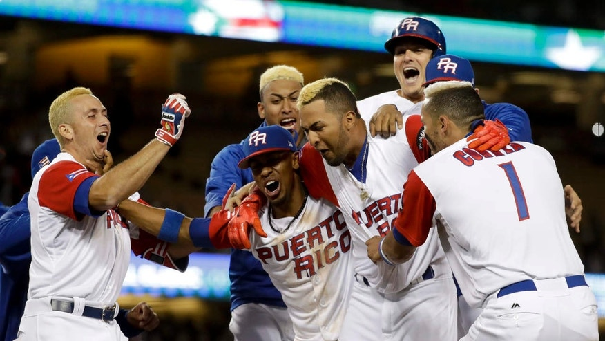 Puerto Rico team members celebrate their win over the Netherlands in a semifinal in the World Baseball Classic in Los Angeles, Monday, March 20, 2017.
