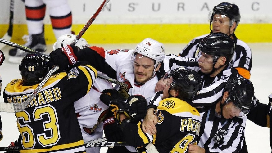 Referees and linesman try to separate Boston Bruins and Ottawa Senators players after the conclusion of an NHL hockey game in Boston, Tuesday, March 21, 2017. The Senators won 3-2. (AP Photo/Charles Krupa)