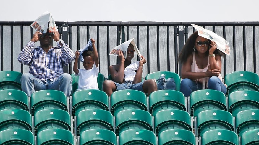 A family shields themselves from the sun as they watch a tennis match between Marcel Granollers, of Spain, and Borna Coric, of Croatia, at the Miami Open, Thursday, March 23, 2017 in Key Biscayne, Fla. (AP Photo/Wilfredo Lee)