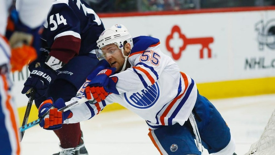 Edmonton Oilers center Mark Letestu, right, reaches out to control the puck as Colorado Avalanche center Carl Soderberg, of Sweden, defends in the second period of an NHL hockey game Thursday, March 23, 2017, in Denver. (AP Photo/David Zalubowski)