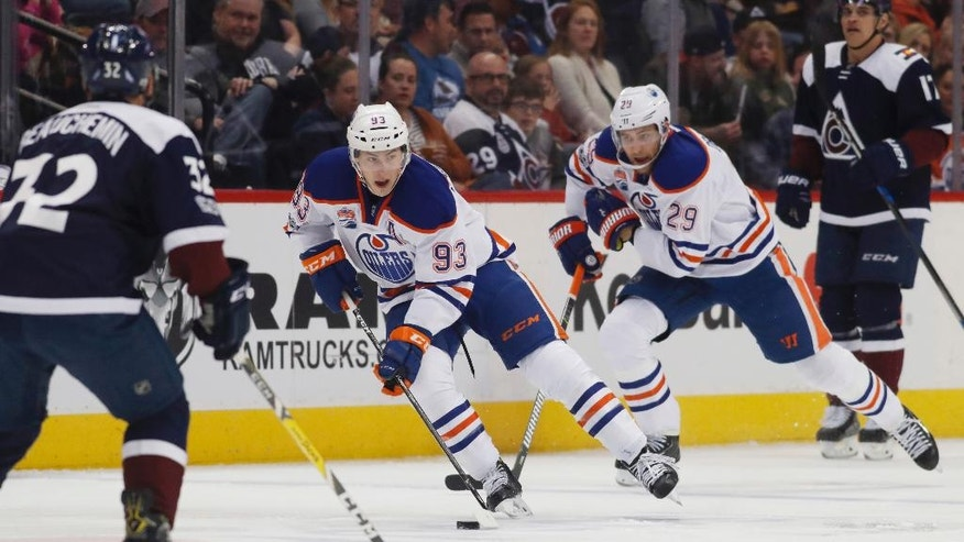 Edmonton Oilers center Ryan Nugent-Hopkins, center, leads center Leon Draisaitl, of Germany, right, down the ice with the puck as Colorado Avalanche defenseman Francois Beauchemin drops back to cover pursues in the second period of an NHL hockey game Thursday, March 23, 2017, in Denver. (AP Photo/David Zalubowski)