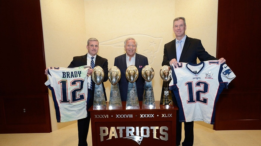 New England Patriots owner Robert Kraft stands between FBI Boston Special Agent in Charge Harold Shaw, left, and Massachusetts State Police Colonel Richard McKeon. Shaw is holding Tom Brady's game-worn jersey from Super Bowl 49, while McKeon is holding Brady's jersey from Super Bowl 51.