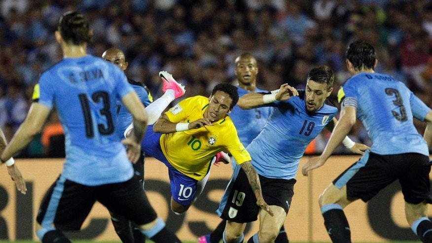 Brazil's Neymar, center, fights for the ball with Uruguay's Sebastian Coates, second from right, during a 2018 World Cup qualifying soccer match in Montevideo, Uruguay,Thursday, March 23, 2017. (AP Photo/Matilde Campodonico)